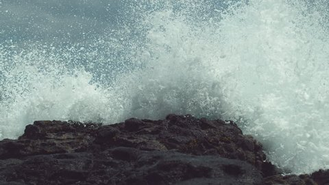 SLOW MOTION, CLOSE UP: Powerful ocean swell hits the tropical black rocky shore and splashes high in the air. Spectacular view of dangerous waves crashing into the tropical beach on Easter Island.