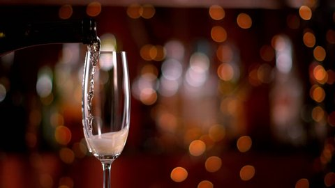 Super slow motion of pouring champagne wine from bottle into goblet. Shot on high speed cinema camera with 1000fps 4K resolution.