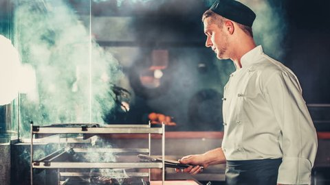 Chef in black apron and hat standing near the brazier whith coals. Cooking beef steak in the interior of modern professional kitchen. Wood burn and air melt from the heat. Blue color filter toning. 4K Cinemagraph