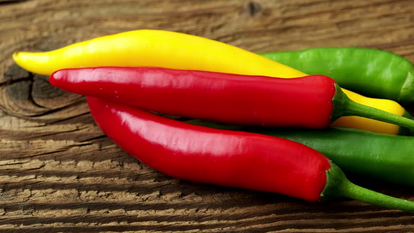 Spicy chilies peppers on wooden background. Colorful peppers on rustic wooden table. Raw healthy food.