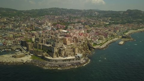 Aerial drone footage of the Italian city of Pozzuoli during on a sunny day.  It is a beautiful coastal city and tourist destination next to Naples.
