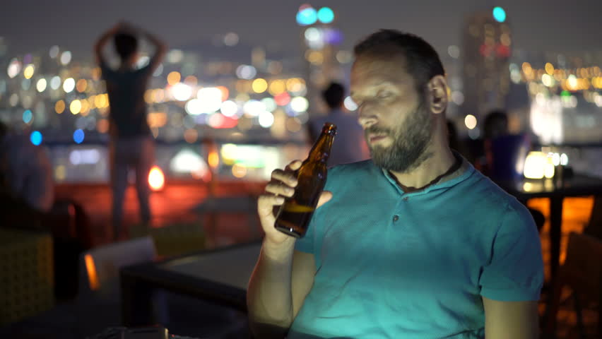Drunk man drinking beer sitting in skybar at night  | Shutterstock HD Video #1012642481