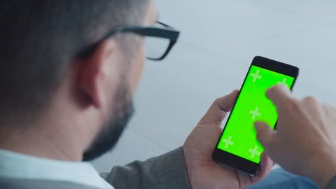 Smartphone vertical orientation with a green screen: shot over the shoulder of a man in glasses. He sits in lobby, looks at screen of mobile phone. Gadgets: social networks, e-mail, business online