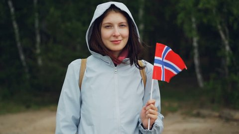 Slow motion portrait of attractive Norwegian sports fan waving official flag of Norway standing in forest and smiling. People, nationality and countries concept.