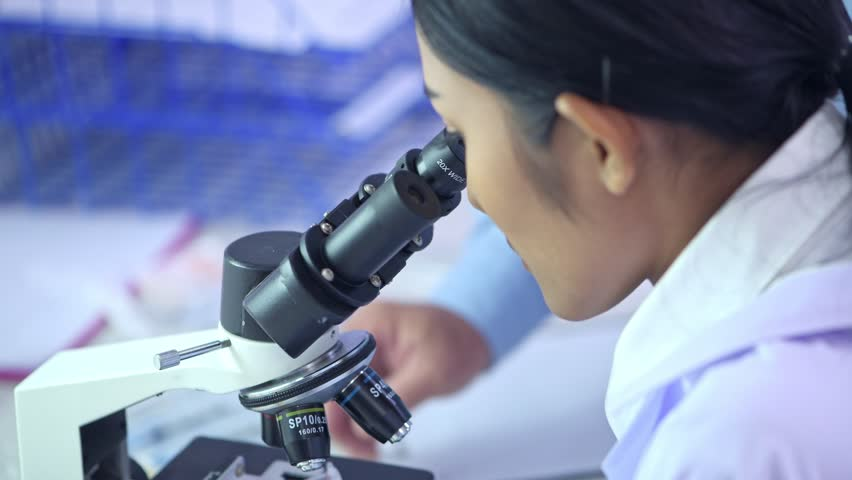 Scientist looking into microscope. Young female scientist looking at microscope to see dna. Close up shot in lab. | Shutterstock HD Video #1012657601