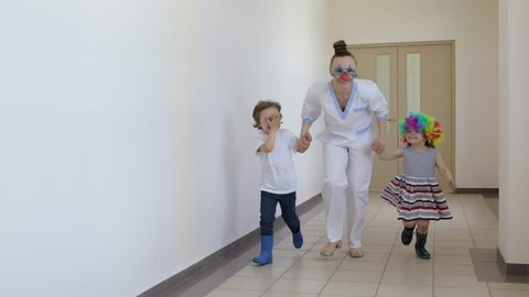 Medical sister in professional uniform with two funny children in the corridor of hospital.