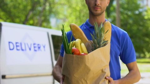 Young deliveryman showing grocery bag, store service, online order shipment