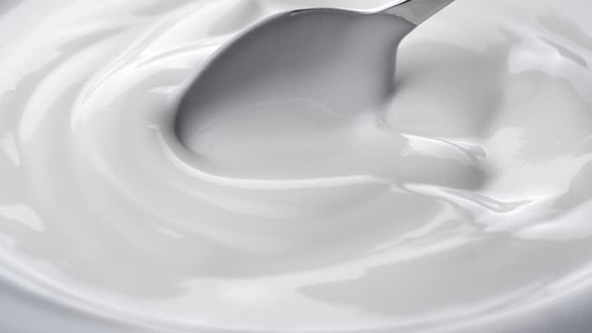 Closeup shot of mixing yogurt with spoon, Rotating