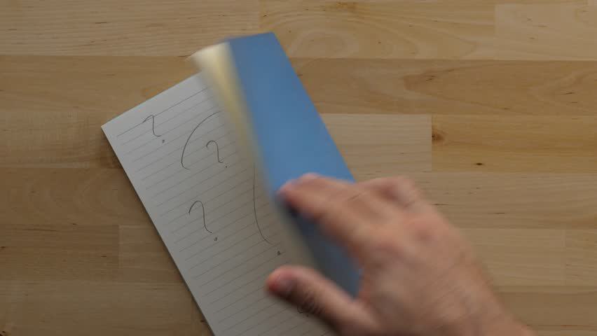 Man flip and close notebook, many question marks written on page. Top down shot of wooden table at home office or studio. Notepad with blue cover remain on desk
