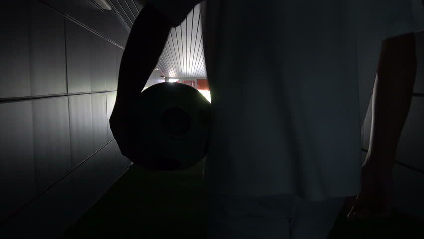 Two football players are walking along a dark tunnel to the football field. View from the back | Shutterstock HD Video #1012709471