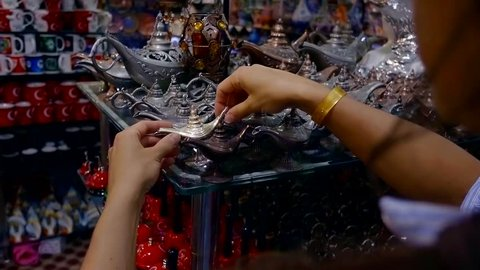 woman is choosing small silver souvenir oil lamp in a gift shop, close-up of hands with good
