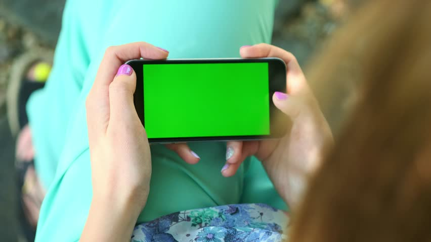 Beautiful girl holding a smartphone in the hands of a green screen green screen, hand of man holding mobile smart phone with chroma key green screen on white background, new technology concept. #1012717841