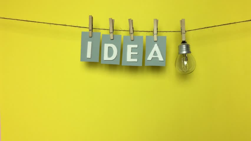 "Word ""idea"" on a string with tweezers and a light bulb on a yellow background. 