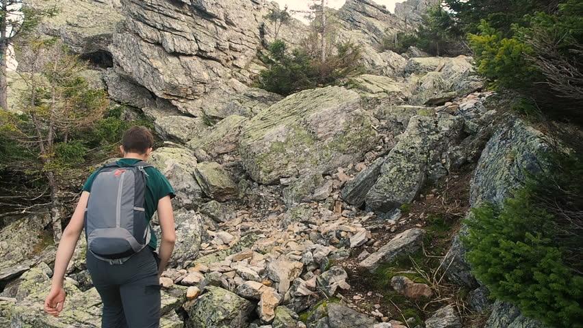 Hiker Climber Climbing Mountain. Rock Climbing Recreation Activity Hiking Active Lifestyle. Rock climber climbing  top of mountain. Young Man Walking Up Mountain Slope Backpacking Summer Climbing