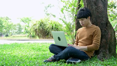 Young man using laptop in park. Sitting on grass near a big tree, relaxing and using a laptop. With copy space.