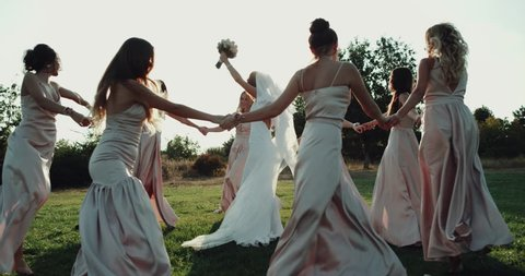 Gorgeous bride and her bridesmaid dancing amazing on the grass with amazing sunlight. red epic