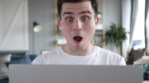 Close Up of Shocked Man Wondering and Working on Laptop