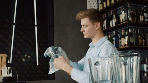 Bartender wiping glasses behind the bar