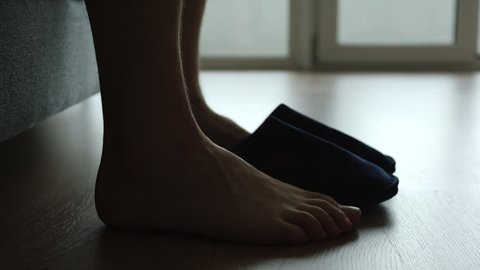 Silhouette of young adult man legs slips a slippers