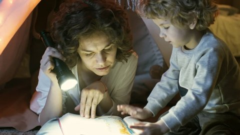 Close up shot of cute little boy pointing at something in fairy tale book and talking to caring mother when reading together using flashlight