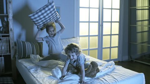 Two adorable children, brother and sister, having fun together and fighting with pillows on bed at night