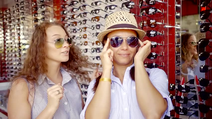adult women are trying on trendy sunglasses in a shop, wearing it, looking on herself and putting off