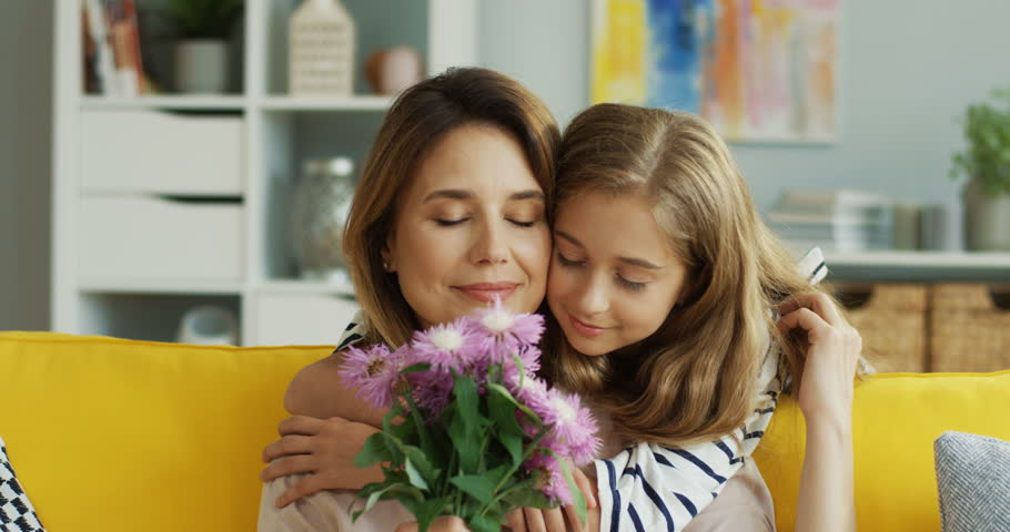 Close up of the beautiful caucasian mother and daughter on the sofa hugging and woman holding a bouquet of flowers her daughter gave her. Portrait. Inside.