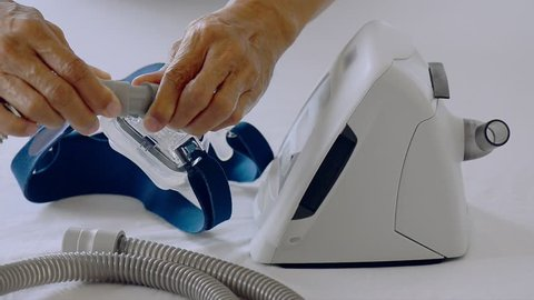 Man hands assembling patient tube to cpap mask and cpap machine in white background, hd video selective focus. Cpap installation .