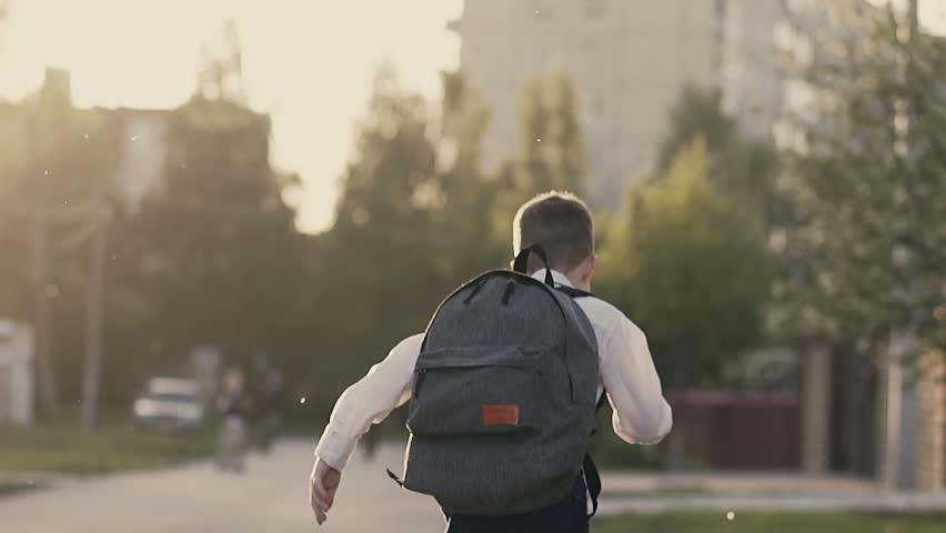 CU, Tracking, Slow motion, Back view shot: Student after school hours runs home.  | Shutterstock HD Video #1012835351