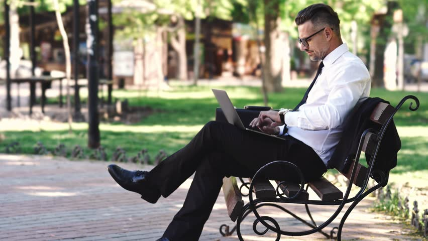Side view of successful businessman dressed in shirt using laptop computer while sitting outside on a bench