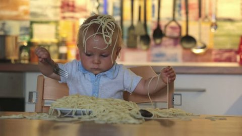 Little baby boy, toddler child, eating spaghetti for lunch and making a mess at home in kitchen