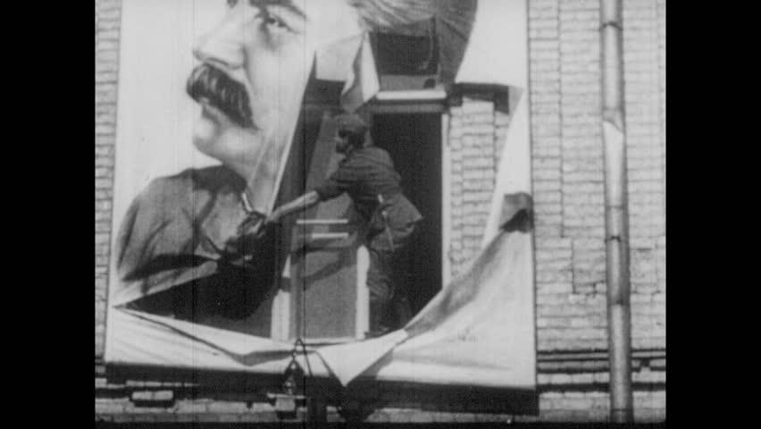 1930s: Man tears down poster of Stalin. Men hammer statues of Stalin. Men topple statues of Stalin. Men hang poster of Hitler in window.