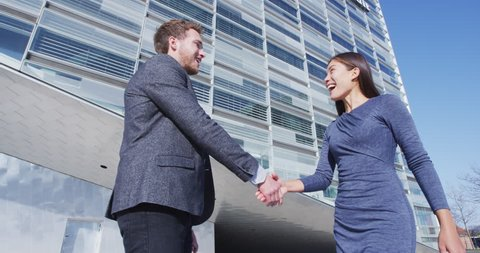 Business People Handshake - business people shaking hands. Handshake between man and woman outdoors by business building. Casual business clothing, young people in their 30s. SLOW MOTION
