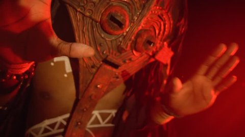 The black shaman in the mask rhythmically shakes his hands in the red light