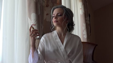 Beauty girl in a white silk dressing gown is spraying a perfume.