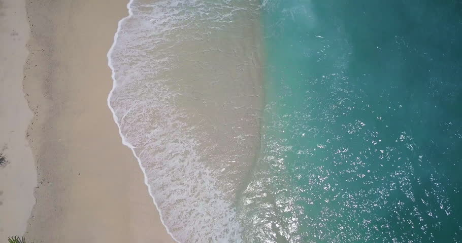 Top camera view over white sand beach and little waves of blue sea or ocean running on the shore. Summer beach background. Sand and sea. Aerial drone slow motion footage Uhd 4K. | Shutterstock HD Video #1012914551