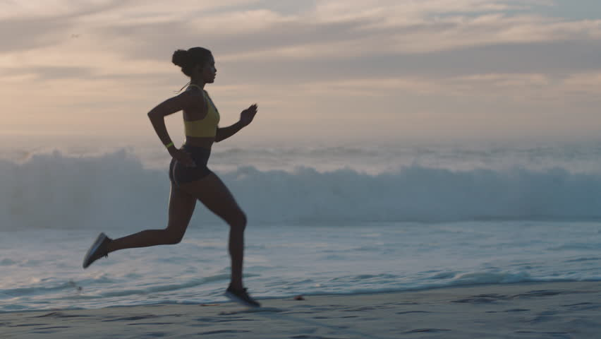young woman athlete running on beach exercising female runner sprinting training in evening seaside background sunset #1012930181