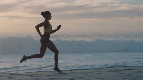 young woman athlete running on beach exercising female runner sprinting training in evening seaside background sunset