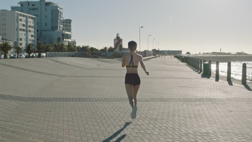 Rear view young asian woman athlete running training cardio enjoying fitness workout lifestyle on early urban seaside morning wearing sportswear relaxed healthy lifestyle | Shutterstock HD Video #1012932791
