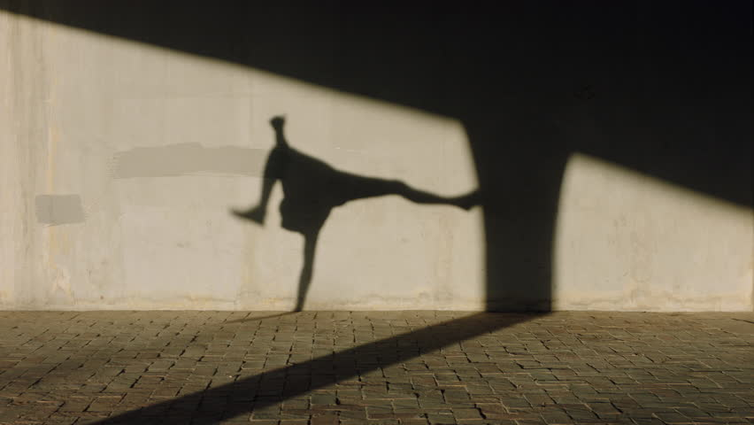 Dancing man young street dancer breakdancing performing various freestyle dance moves fit mixed race male practicing in city at sunset with shadow on wall