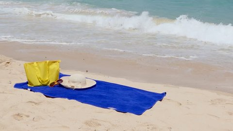 blue towel for sunbath,glasses and Yellow bag on the beach, beautiful Kata Noi beach Phuket Thailand