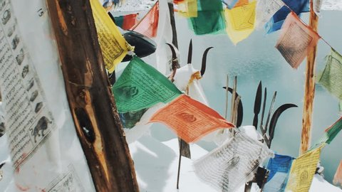 prayer flags Lungta in the temple near the winter lake in the Himalayas