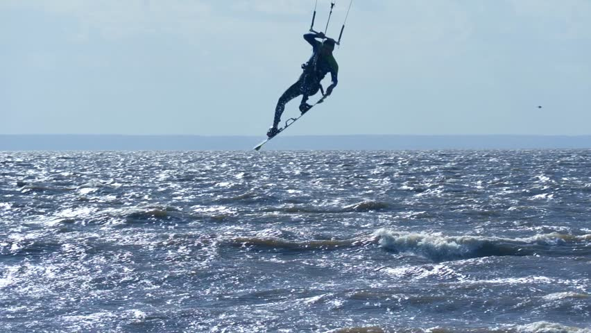 SLOW MOTION: Kiteboarder rides on the board on the waves. Summer sunny evening. | Shutterstock HD Video #1012973021