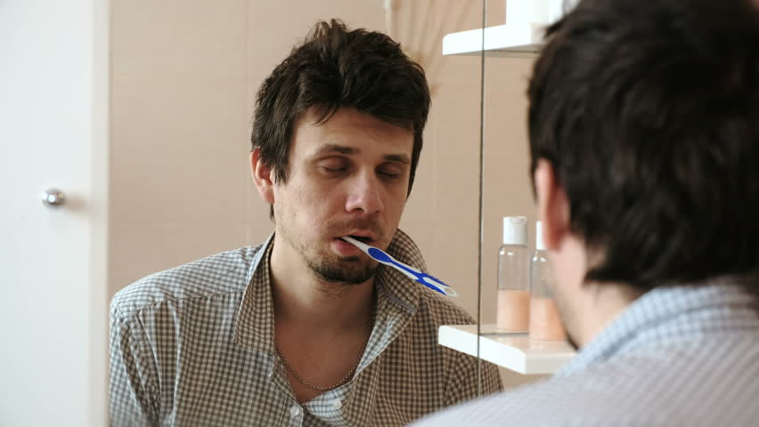 Tired sleepy man with a hangover who has just woken up brush his teeth, looks at his reflection in the mirror.