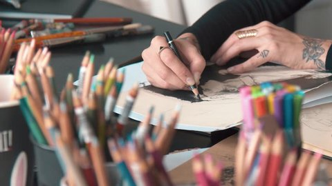 Busy female artist making black background on drawing of a man, depicting imagined idea on the paper, working at the desk in art studio