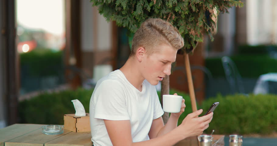 A young man in a cafe uses a phone. The guy communicates online. in slow motion | Shutterstock HD Video #1012978871