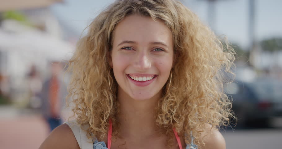 portrait of attractive blonde woman tourist running hand through hair smiling confident enjoying relaxed sunny day on beachfront #1012994651