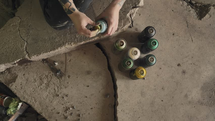 A young graffiti artist chooses a jar of aerosol paint and begins to paint. Look from above