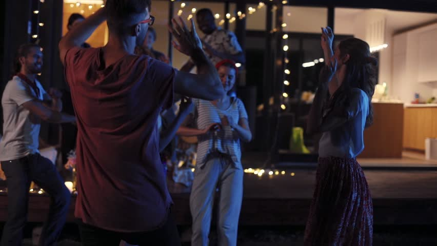 Beautiful friends dancing near modern house in evening. Young people having fun together, celebrating in the open air. Party. Summertime. Outside.   Shutterstock HD Video #1013038451