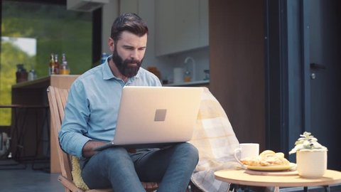 Attractive focused brown-haired man with beard wearing shirt and trousers looking at screen of laptop. Serious businessman working at home, holding cup in hand. Outdoors.